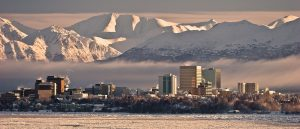 Escape Case team building in Anchorage, Alaska. Anchorage City skyline overseeing the bay. A thick fog overcasts the city before the mountain range is shown in the background on an overcast day.