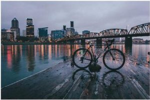 Escape Case team building in Portland, Oregon. Late evening skyline, the city lights reflected over the river before it. A grand bridge spans the river of the late evening. A bicycle stands before the before the river and the city upon a sodden dock.